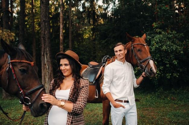 Een zwanger meisje in een hoed en een man in witte kleren staan naast paarden in het bos in de natuur