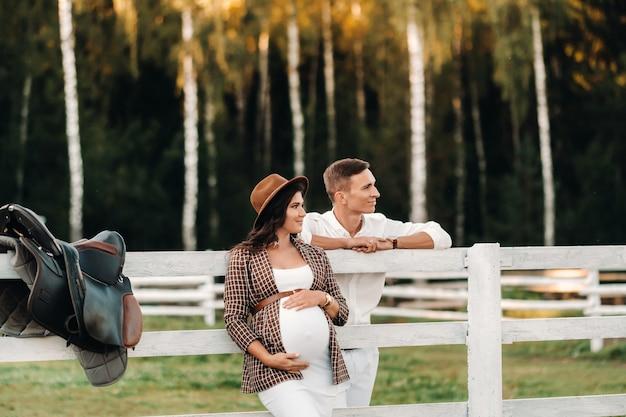 Een zwanger meisje in een hoed en haar man in witte kleren staan bij zonsondergang naast een paardenkraal. een stijlvol stel wacht op een kind in de natuur.