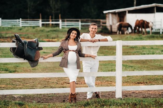 Een zwanger meisje in een hoed en haar man in witte kleren staan naast de paardenkraal. een stijlvol stel wachtend op een kind staat op straat bij de paardenkraal.