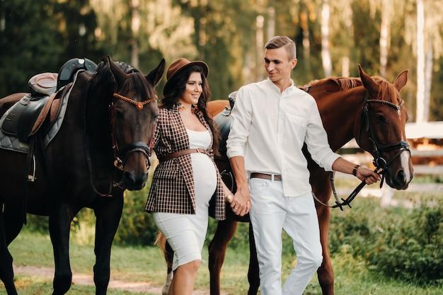Een zwanger meisje in een hoed en haar man in witte kleren staan naast paarden in het bos in de natuur