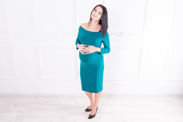 Een zwanger meisje in een jurk met een dikke buik. hoge kwaliteit foto