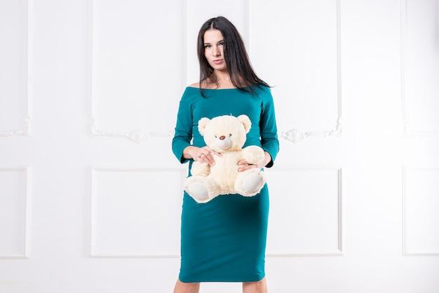 Een zwanger meisje in een jurk met een teddybeer in haar handen. hoge kwaliteit foto