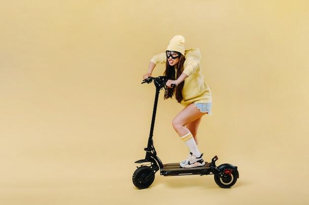 Een zwanger meisje in gele kleren op een elektrische scooter op een afgelegen gele achtergrond.