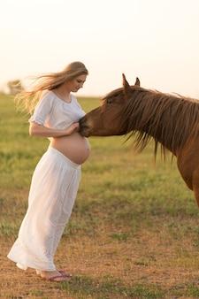 Een zwanger meisje in het wit communiceert met een paard op een groene weide bij zonsondergang. therapie en ontspanning voor zwangere vrouwen. antistress-therapie.