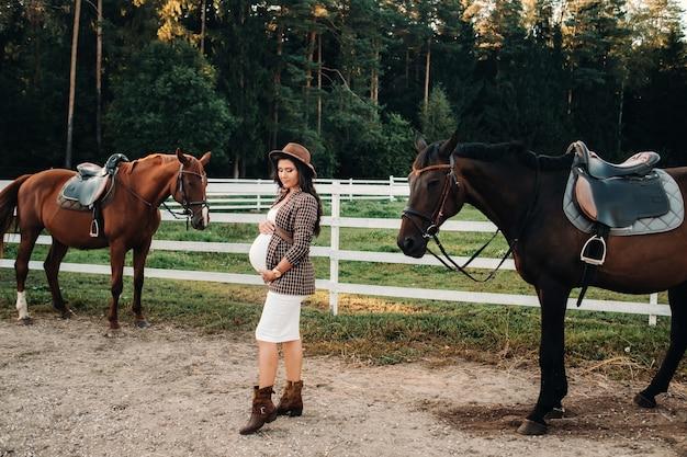 Een zwanger meisje met een dikke buik in een hoed naast paarden in de buurt van een paddock in de natuur