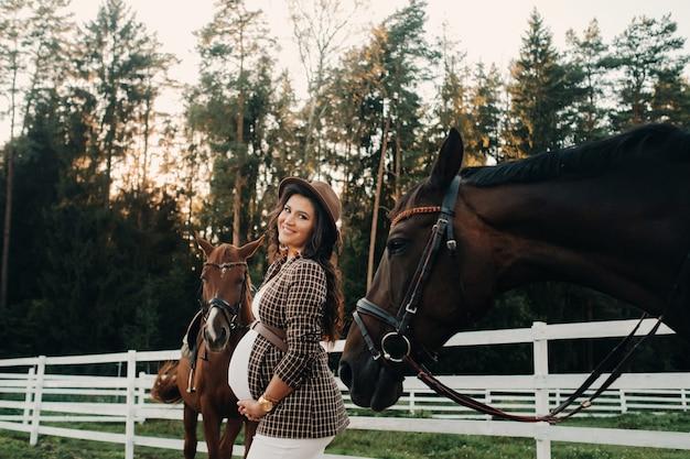 Een zwanger meisje met een grote buik in een hoed naast paarden in de buurt van een paddock in de natuur. stijlvolle zwangere vrouw in een bruine jurk met paarden.