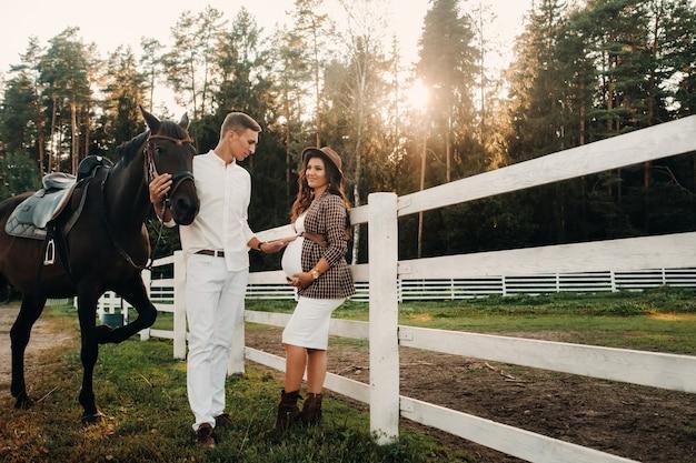 Een zwanger meisje met een hoed en een man in witte kleren staan naast paarden bij een wit hek. stijlvolle familie die wacht op een kind dat in de natuur wandelt.