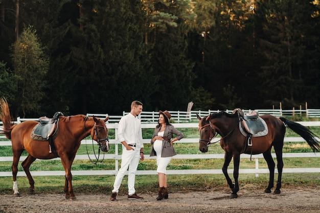 Een zwanger meisje met een hoed en een man in witte kleren staan naast paarden bij een wit hek.