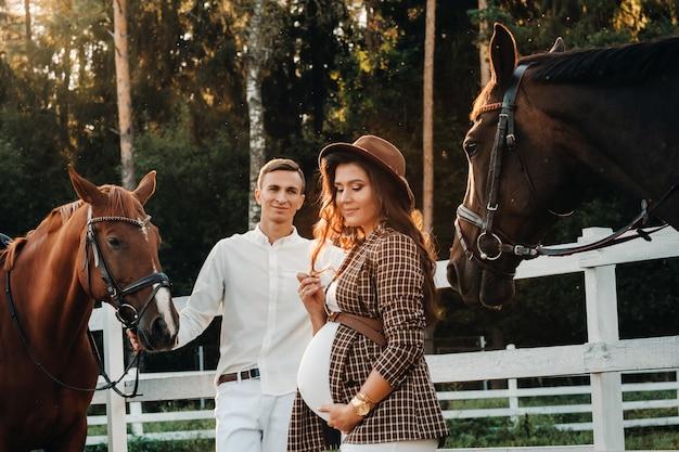 Een zwanger meisje met een hoed en een man in witte kleren staan naast paarden bij een wit hek