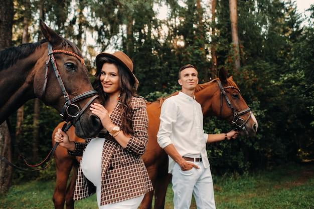 Een zwanger meisje met een hoed en een man in witte kleren staan naast paarden in het bos in de natuur