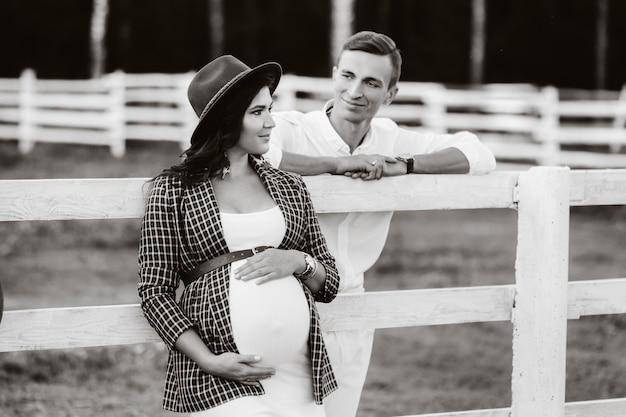 Een zwanger meisje met een hoed en haar man in witte kleren staan naast de paardenstal. een stijlvol stel dat op een kind wacht, staat op straat in de buurt van de paardenstal. zwart-wit foto.