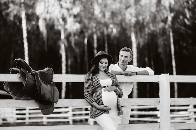 Een zwanger meisje met een hoed en haar man in witte kleren staan naast een paardenstal bij zonsondergang. een stijlvol stel wacht op een kind in de natuur. zwart-wit foto