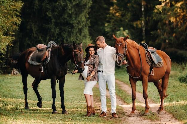 Een zwanger meisje met een hoed en haar man in witte kleren staan naast paarden in het bos in de natuur. stijlvolle zwangere vrouw met een man met paarden.