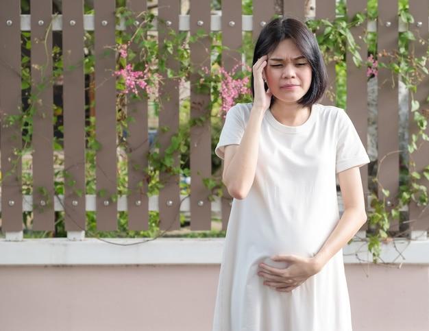 Een zwangere aziatische moeder in een lange witte jurk maakt zich zorgen over haar buikpijn in de buitenlucht.