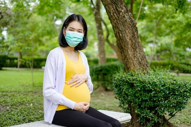 Een zwangere moeder met een paarsgele jurk en een masker zit op een stenen stoel in de tuin.