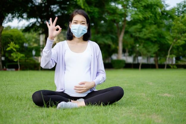 Een zwangere moeder met paarse en witte vrijetijdskleding en een masker zit in de tuin met de duimen omhoog ok.