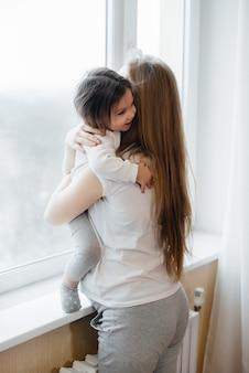 Een zwangere moeder staat met haar dochtertje bij het raam.