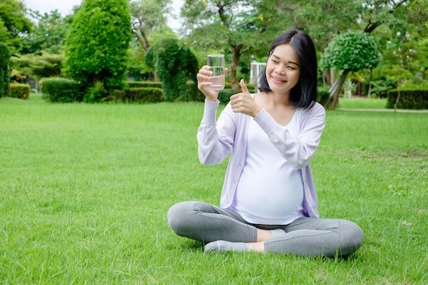 Een zwangere moeder zit met een glas schoon drinkwater voor een goede gezondheid. en duim omhoog