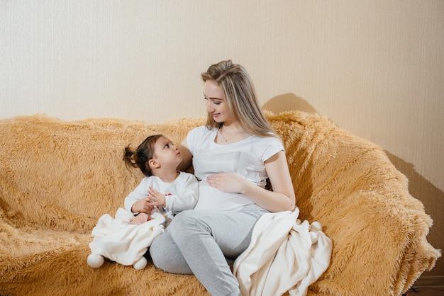 Een zwangere moeder zit op de bank met haar dochtertje en speelt met een gadget