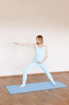 Een zwangere vrouw beoefent yoga in de studio
