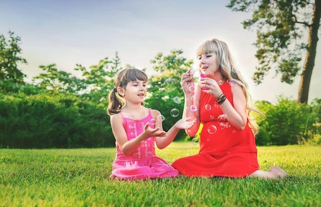Een zwangere vrouw blaast zeepbellen met haar dochter