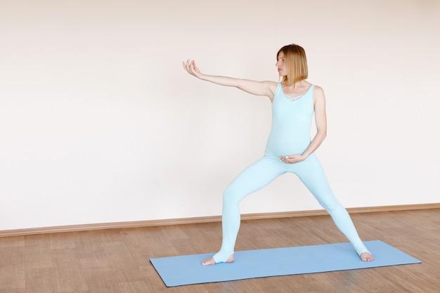 Een zwangere vrouw doet yoga op een lichte achtergrond. zwangere yoga