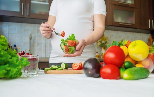 Een zwangere vrouw eet groenten en fruit