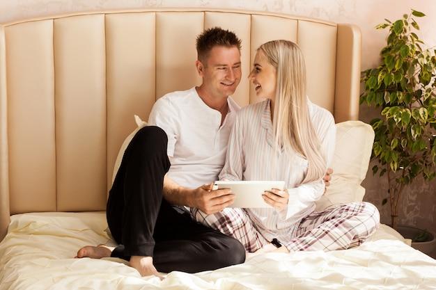 Een zwangere vrouw en een man liggen thuis op het bed.