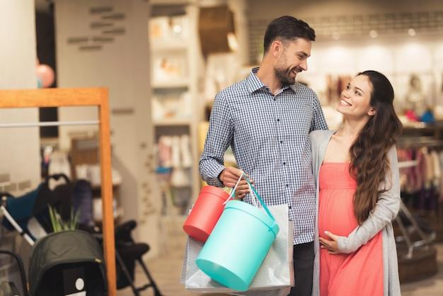 Een zwangere vrouw en een man poseren voor een camera.