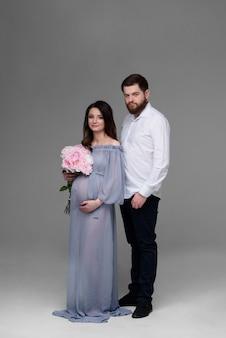 Een zwangere vrouw en haar man knuffelen op een grijze achtergrond in de studio.