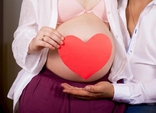 Een zwangere vrouw houdt een hartvormig papier op haar buik.