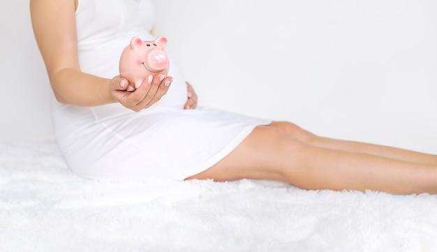 Een zwangere vrouw houdt een spaarvarken.