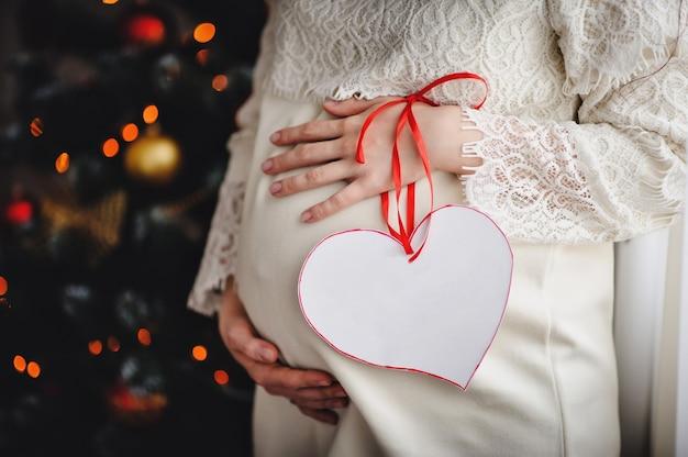 Een zwangere vrouw houdt haar armen om de ronde buik. bevat een versierd hart met een lint. uitzicht op de maag zwangere vrouw. wachten op een baby. gelukkig familieportret, concept van een vakantie met het gezin.