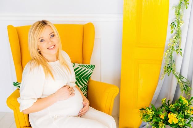 Een zwangere vrouw houdt haar armen op haar buik zittend in een zachte fauteuil