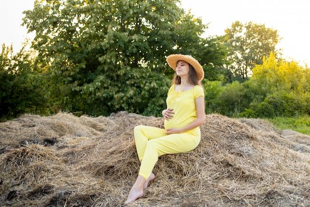 Een zwangere vrouw in donkere kleren en een hoed zit in de zomer in een veld op stro