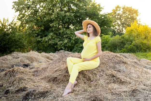 Een zwangere vrouw in donkere kleren en een hoed zit in een veld op stro in de zomer