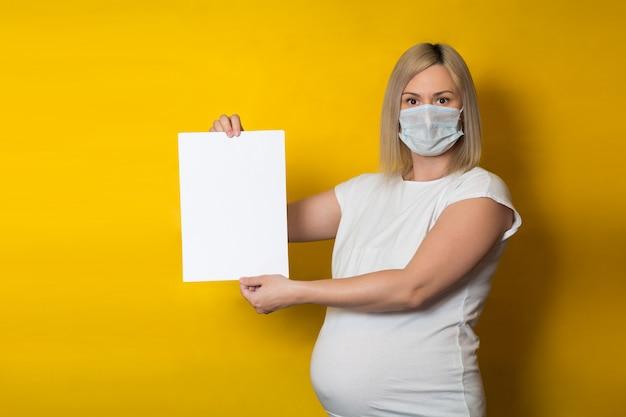 Een zwangere vrouw in een beschermend masker houdt een blanco verticaal vel papier op een gele muur