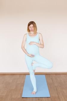 Een zwangere vrouw in een blauw yogapak omhelst haar buik en staat op één been in een lichte studio