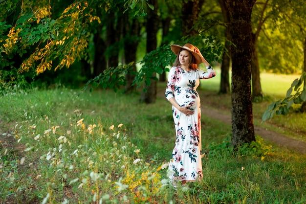 Een zwangere vrouw in een jurk en hoed loopt in de zomer door het bos, een wandeling van een zwanger meisje in de natuur