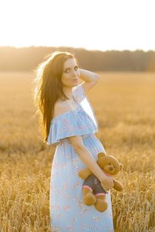 Een zwangere vrouw in een lange blauwe jurk in een tarweveld bij zonsondergang met een gevuld beer speelgoed en lachend