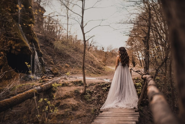 Een zwangere vrouw in een lichte lange jurk