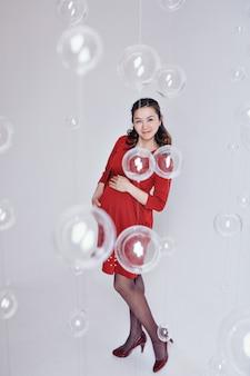 Een zwangere vrouw in een rode jurk. concept van moederschap, familiedag, moederdag, ivf