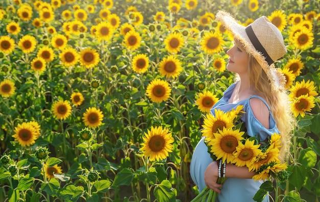 Een zwangere vrouw in een veld met zonnebloemen