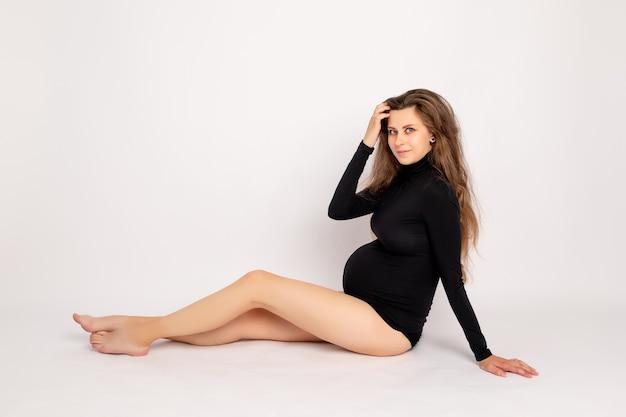 Een zwangere vrouw in een zwarte bodysuit ligt