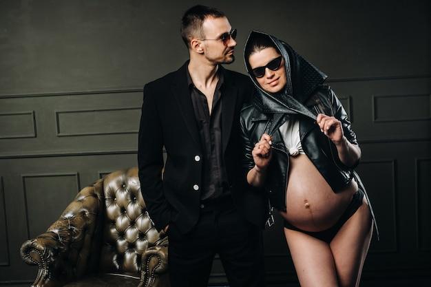 Een zwangere vrouw in zwarte kleding en een hoofddoek en een man in een pak in een studio op een donkere achtergrond.