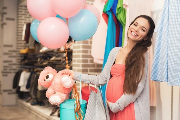 Een zwangere vrouw kiest babyartikelen in de winkel.