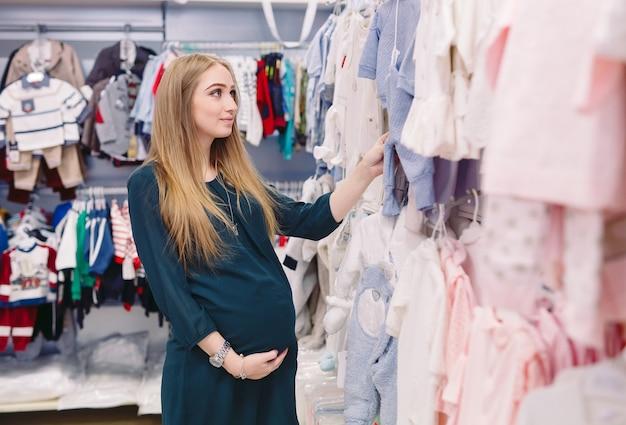 Een zwangere vrouw kiest kinderkleding in de winkel.