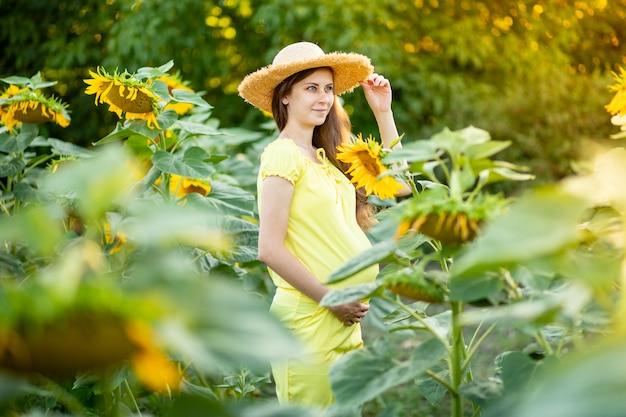 Een zwangere vrouw loopt in een veld met zonnebloemen