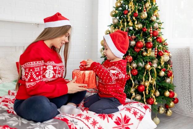 Een zwangere vrouw met een jongetje in een rode trui en hoeden geeft geschenken onder de kerstboom thuis op het bed en verheugt zich in het nieuwe jaar en kerstmis