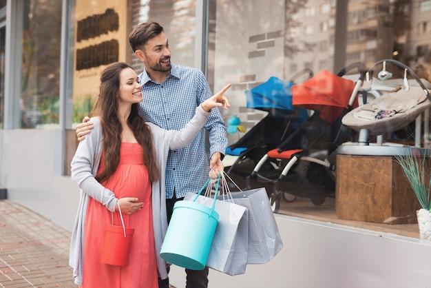 Een zwangere vrouw met een man die langs de winkel loopt.